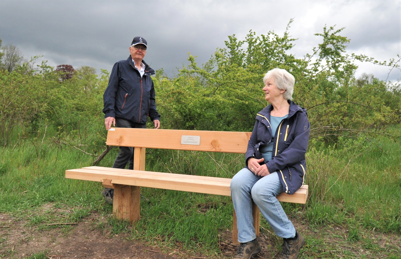 Twee wandelaars, Attie en Dick Goedhart, rusten even uit op de bank die herinnert aan Cees Kwakernaak, Mister Renkums Beekdal.