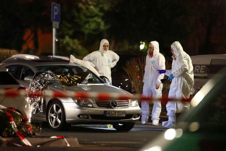 Forensische experts bij een auto die tijdens een van de schietpartijen beschadigd raakte. Beeld REUTERS