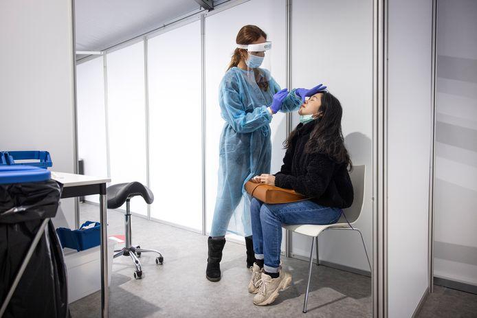 Een vrouw neemt een coronatest af bij een andere vrouw.