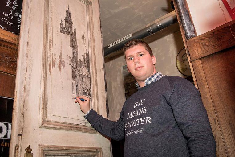 Djordy Rondelez (21) tekent een foto na op een binnendeur van cultuurcafé K-trolle.
