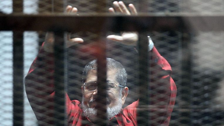 Mohammed Morsi tijdens zijn proces in Caïro in juni. Beeld AFP