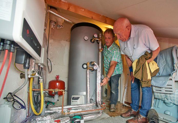 Jan van Erp praat met Peter van Hoogstraten (groene ruitjesblouse) over het gasvrij maken van de woning uit 1976, van laatstgenoemde in Berghem.