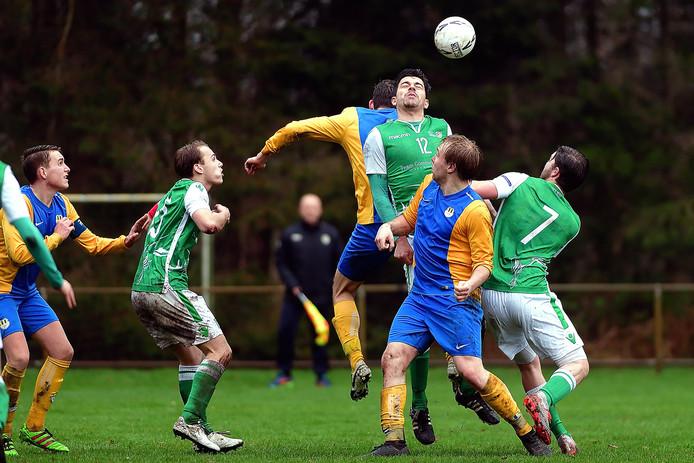 Een van de vele duels in Halsteren tussen Vrederust (groen) en Internos (geel-blauw). Robbie van Nieuwburg (nummer 12/Vrederust) verliest een kopduel van Internos-speler Rick de Vlam.