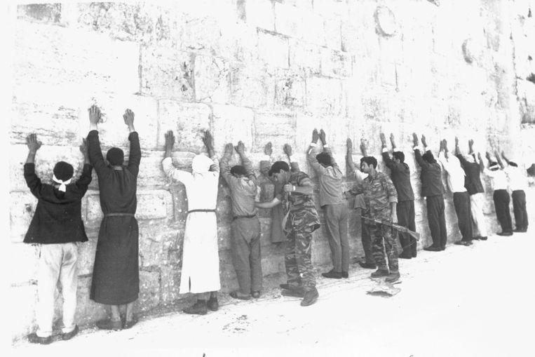 Twee Isräelische militairen fouilleren een groep gevangengenomen Jordaniërs in Jeruzalem tijdens de zesdaagse oorlog. Beeld AP