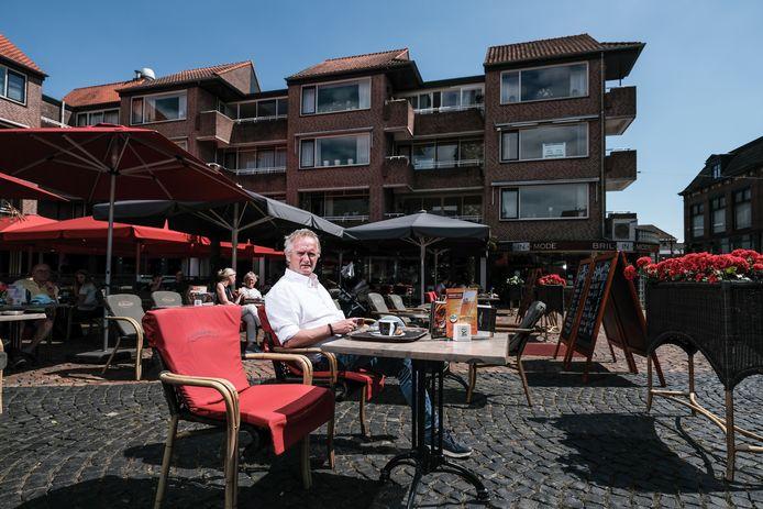 Hans Tenbergen van La Promenade op zijn terras op de Markt in Winterswijk, met aan de rechterkant op de foto het appartement (het middelste) dat hij gratis aanbiedt.