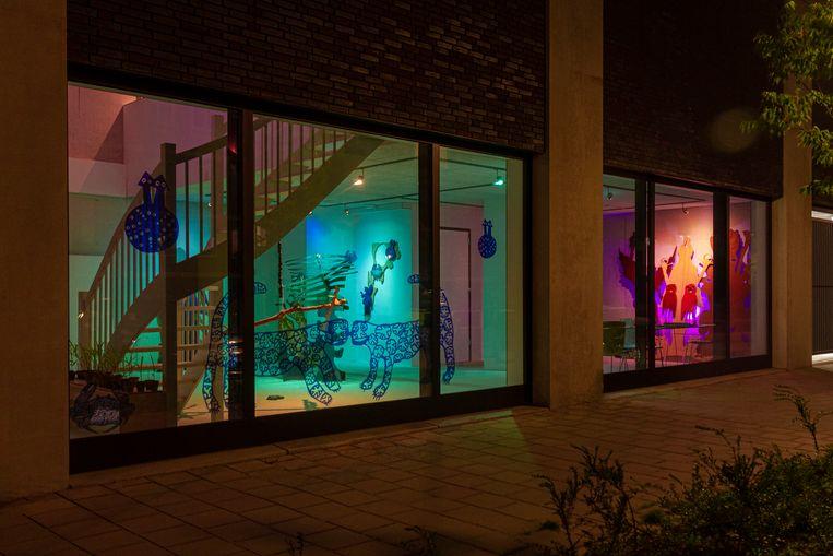 Het interieur van Bureau Postjesweg in Amsterdam-Nieuw-West wordt 's avonds kleurrijk verlicht. Beeld Jitte Hoekstra