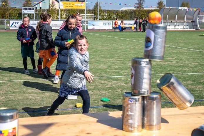 Spelletjeskoningsdag op de velden van de korfbalvereniging. Jeanne (6) gooit de blikken omver.