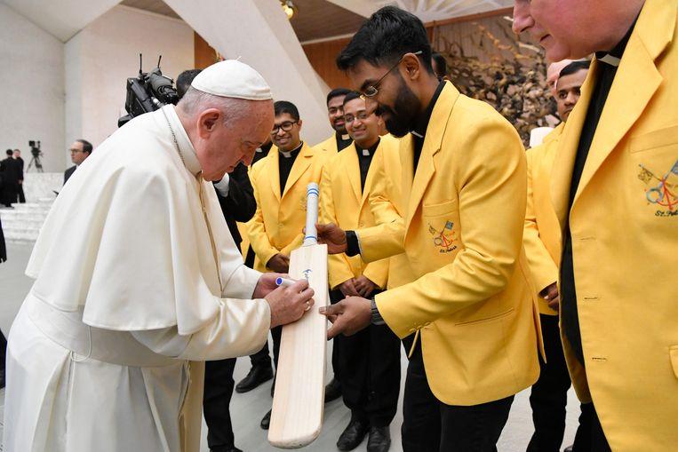Paus Franciscus signeert een cricketbat van het nationale cricketteam van Vaticaanstad. Beeld EPA