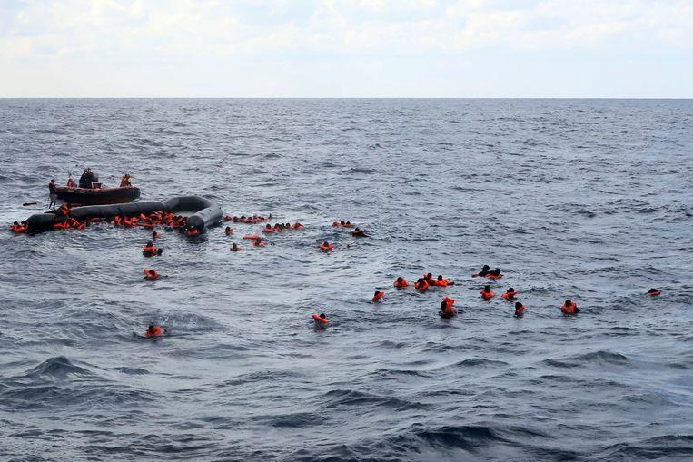 Bootvluchtelingen worden op de Middellandse Zee gered door de  humanitaire organisatie Open Arms nadat hun veel te kleine en instabiele rubberboot kapot gegaan is in het water. Beeld AP