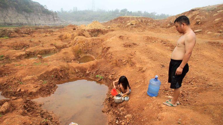Een meisje en haar vader halen water bij een bijna opgedroogd reservoir in Centraal-China. Beeld afp