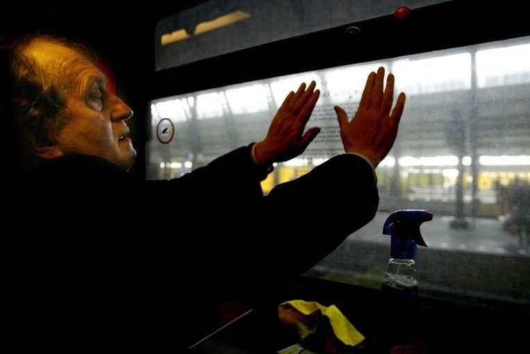 Hangt, in zijn rol van Dichter des Vaderlands, een gedicht op in een trein vanwege de vijfde Gedichtendag in 2004. Beeld ANP
