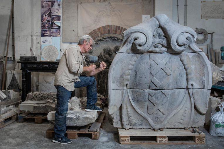 Restaurator Tobias Snoep werkt aan het herstel van de gevelsteen met het wapen van Amsterdam Beeld Dingena Mol