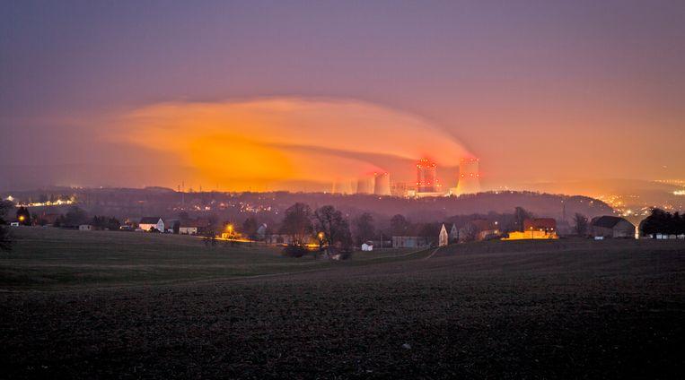 Uitzicht vanuit Duitsland op de verlichte koeltorens van de Turow energiecentrale in Bogytynia, Polen. Beeld Getty Images