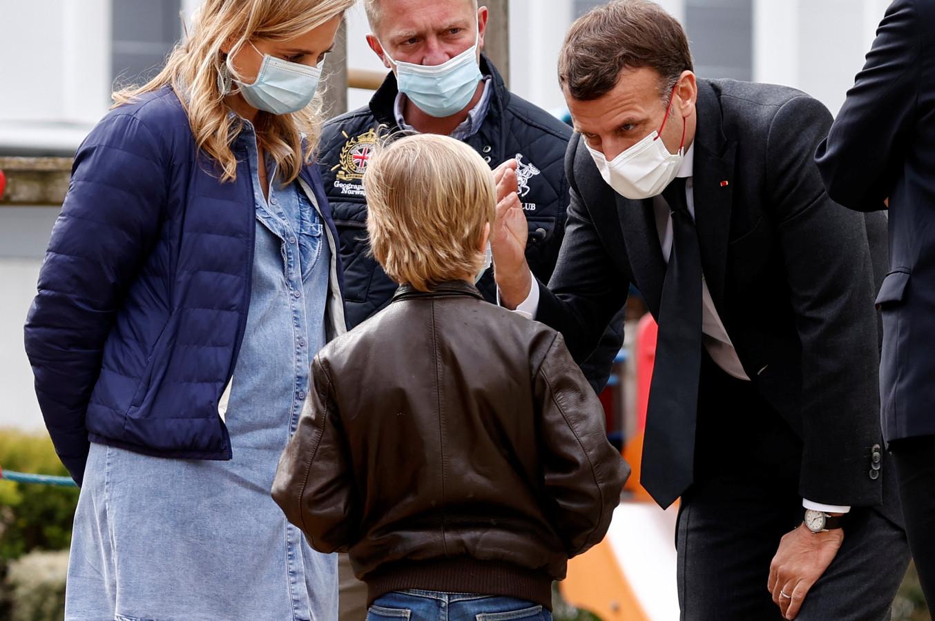 President Emmanuel Macron (rechts) praat met een kind tijdens zijn bezoek aan de psychiatrische afdeling van een ziekenhuis in Reims.