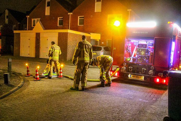 Brandweerlieden spoelen het riool door.