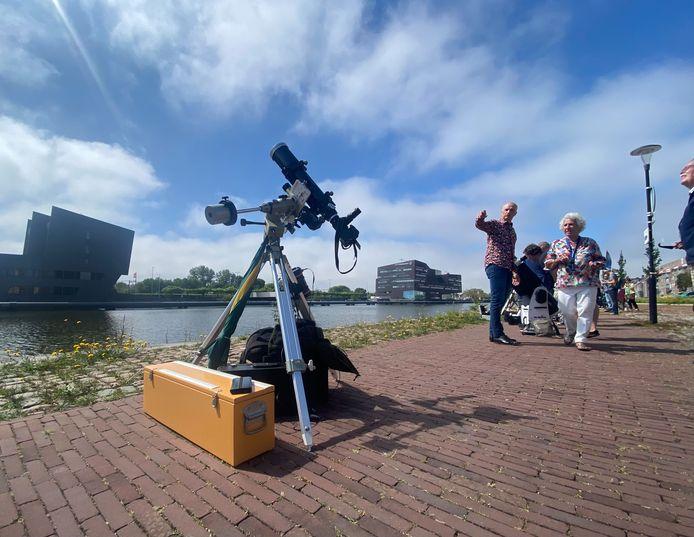 Eén van de elf telescopen die donderdagochtend op de Middelburgse Loskade stonden opgesteld. Op de achtergrond maakt Ben Lap mevrouw Van den Bosch-Van Dillen wegwijs in de sterrenkunde.