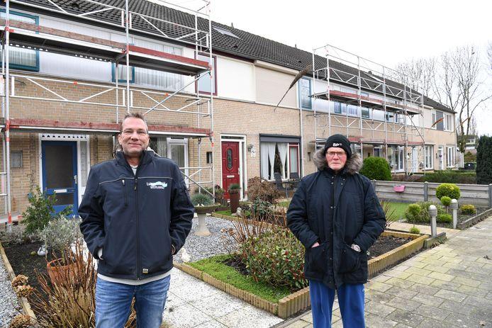 Bewoners John Langermans (l) en Henk Luijbregts voor de rij huurwoningen waar de steigers staan, met daar tussenin een koophuis.