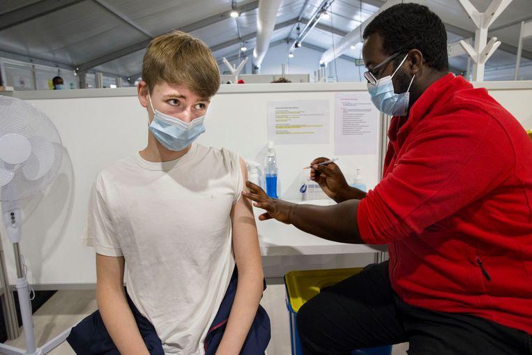 In het Zuid-Hollandse dorp Poortugaal krijgt een tiener een coronaprik. Met een speciale campagne gericht op jongeren wil de overheid de vaccinatiegraad onder 12- tot 18-jarigen verhogen. Beeld Arie Kievit