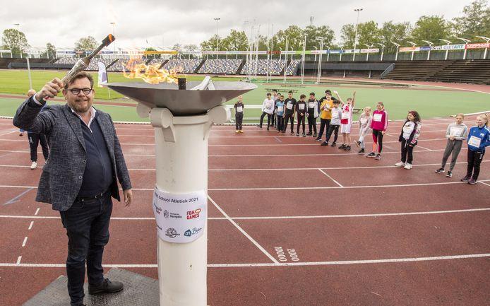 Hans Kloosterman ontsteekt het 'Olympische vuur': de Spelen van Hengelo kunnen beginnen. Op de achtergrond leerlingen Lena (in het roze) en Sam (rood-wit).
