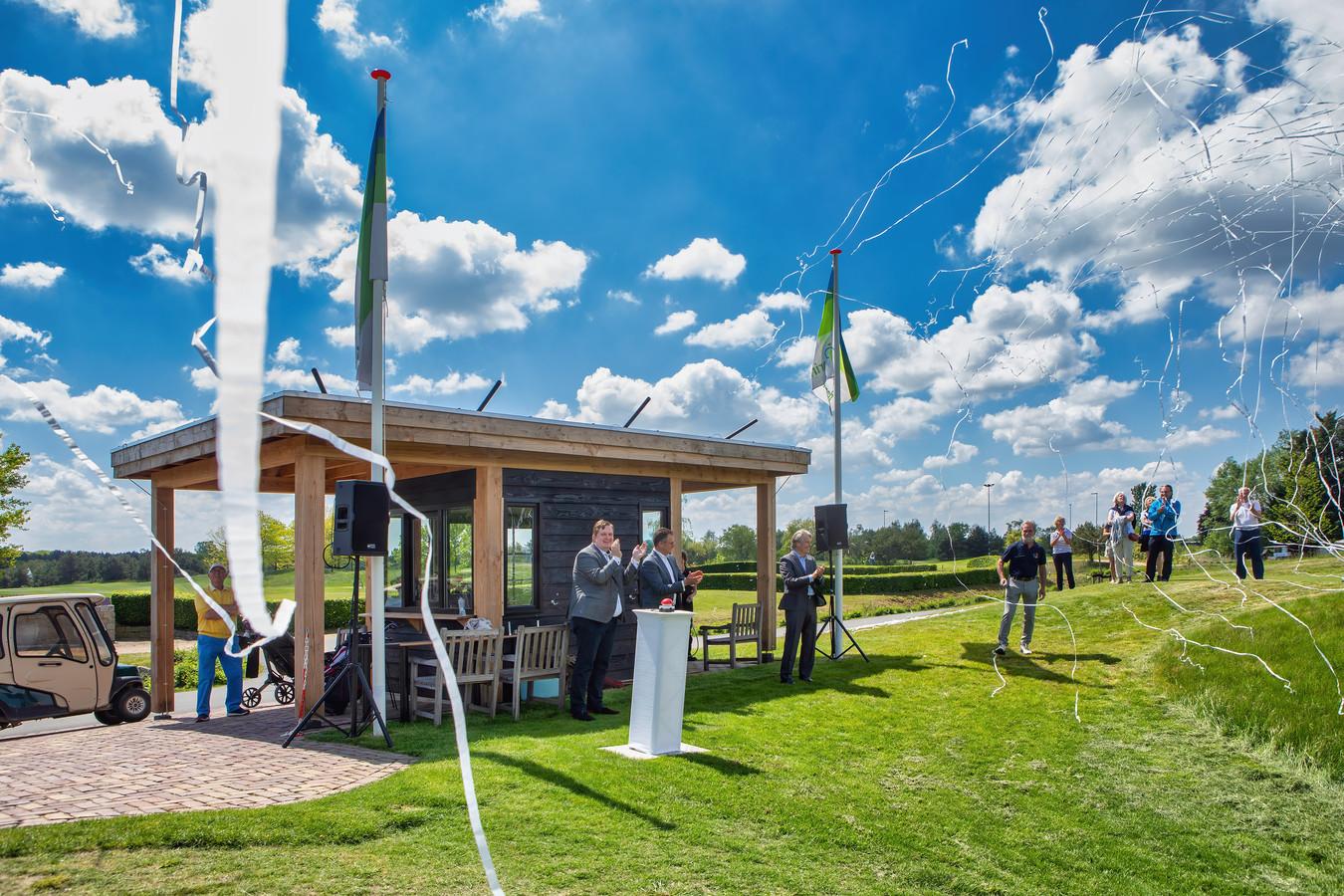 Bij golfclub Princenbosch in Molenschot is de nieuwe 9 holes par 3 baan officieel geopend door wethouder David Vermorken, die zojuist op de knop op de paal waar hij links naast staat heeft gedrukt bij wijze van openingshandeling. Confetti vliegt in het rond en met het nodige tromgeroffel is het officieel.