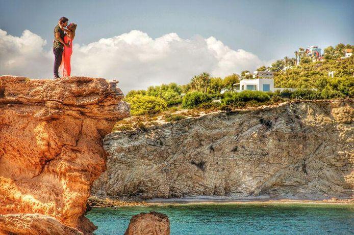 Het verlovingsgeluk vereeuwigd op de rotsen van Ibiza, met rechts de villa waar het koppel deze zomer verblijft.