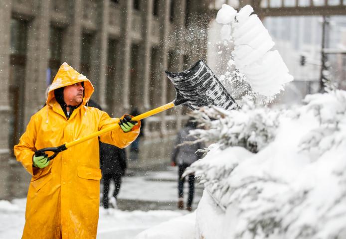 Een gemeentewerker schept de sneeuw opzij op Michigan Avenue in Chicago om de stoep vrij te houden. Scholen en bedrijven houden hun deuren gesloten nu er nog meer sneeuwval is voorspeld. Foto Tannen Maury