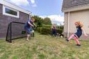 Mark van Rijswijk aan het voetballen in de tuin van zijn huis in Oldemarkt met zijn dochters Sylke en Nynthe.