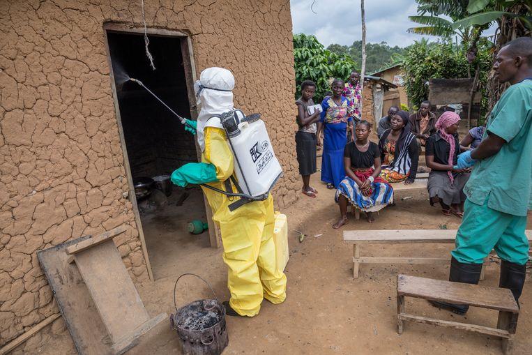 Terwijl bewoners en buren toekijken, wordt het huis van een ebolaslachtoffer ontsmet.  Beeld  Sven Torfinn