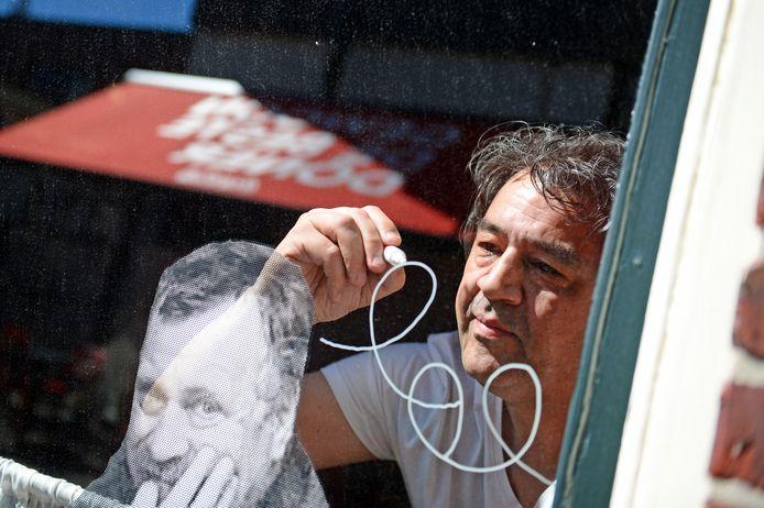 Roel Dikken aan het tekenen op een raam van het Bolwerk.