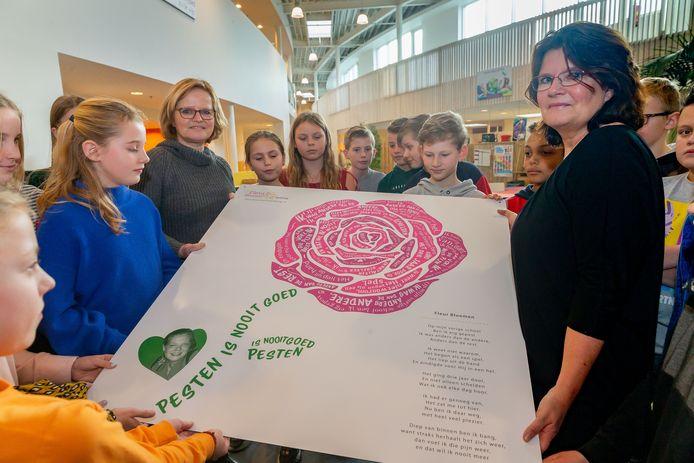 Petra Lueb en Anneke Bloemen geven het bord aan leerlingen van OBS Sprinkels in Meppel, de oude basisschool van hun nichtje en dochter Fleur Bloemen.