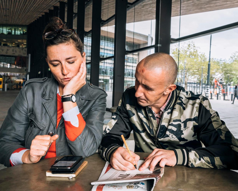 Anna Bartmann en dakloze Szymon bellen op het Centraal Station in Rotterdam naar een uitzendbureau.  Beeld Rebecca Fertinel