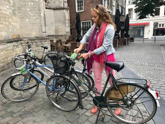 Wethouder Greetje Bos labelt een verkeerd gestalde fiets naast de Grote Kerk op de Grote Markt in Breda.