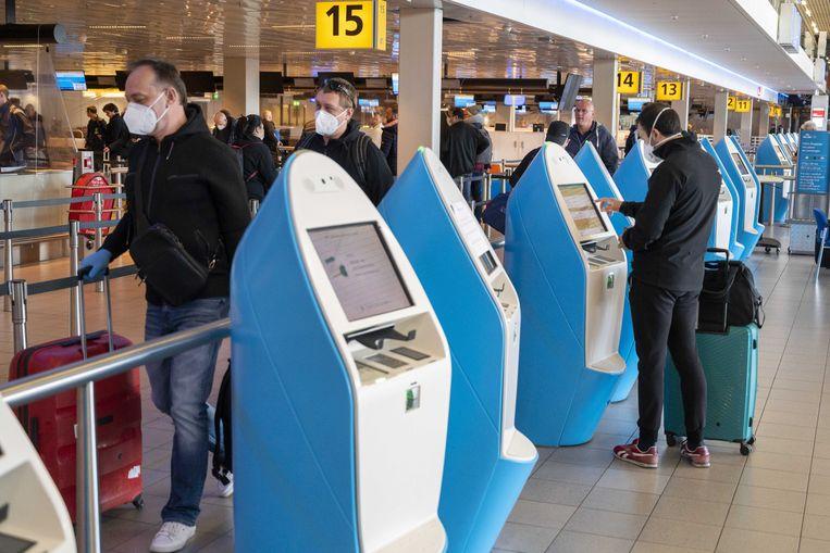 Reizigers met mondkapjes maandag op luchthaven Schiphol. Beeld Evert Elzinga / ANP