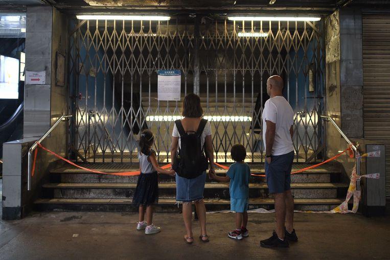 Een gezin staat voor de gesloten deuren van een metrostation in Hongkong.