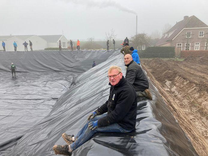 Zo'n veertig mannen uit Hedikhuizen helpen bij het aanbrengen van een enorm 'zeil' in het waterbassin van tomatenkwekerij Pijpers in Hedikhuizen. In het bassin komen mogelijk zonnepanelen te liggen, die Hedikhuizen Duurzaam dan gaat gebruiken.
