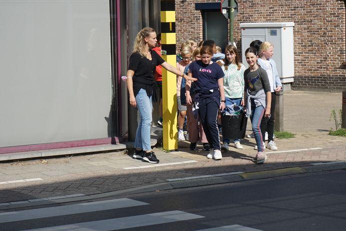 Een juf houdt enkele leerlingen tegen aan de oversteekplaats. Niet alle chauffeurs stoppen zomaar.