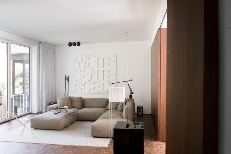 De betimmering van de muren in Amerikaanse eik warmt het gehele appartement op en is een knipoog naar de originele modernistische stijl van het huis.  Beeld Verne