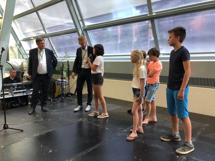 Burgemeester Bakermans interviewt de leerlingen van basisschool De Wizzert over hun plan voro een kindergemeenteraad. Dat was in juni 2019, de raad is nu een feit.
