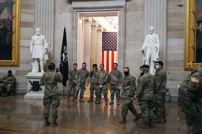 Militairen van de National Guard poseren in de centrale ruimte van het Capitool tijdens de impeachmentprocedure tegen oud-president Trump.  Beeld AFP