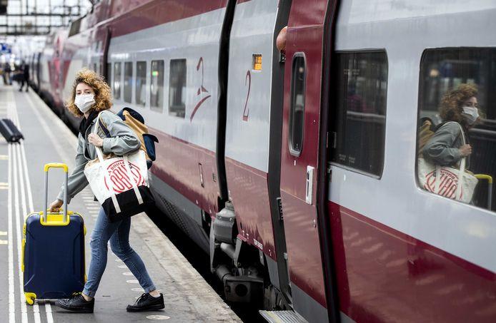 Een treinreiziger met mondmasker op het perron van station Amsterdam Centraal.
