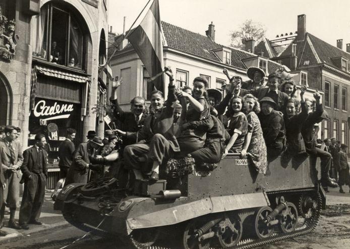 Afbeelding van een brenguncarrier van het 49th Reconnaissance Regiment (Polar Bears) afgeladen met feestende mensen, in de Korte Jansstraat te Utrecht, tijdens de intocht van de geallieerden.