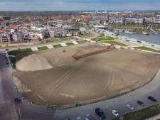 Een kade met een berg: bult zand siert Tielse Waalkade