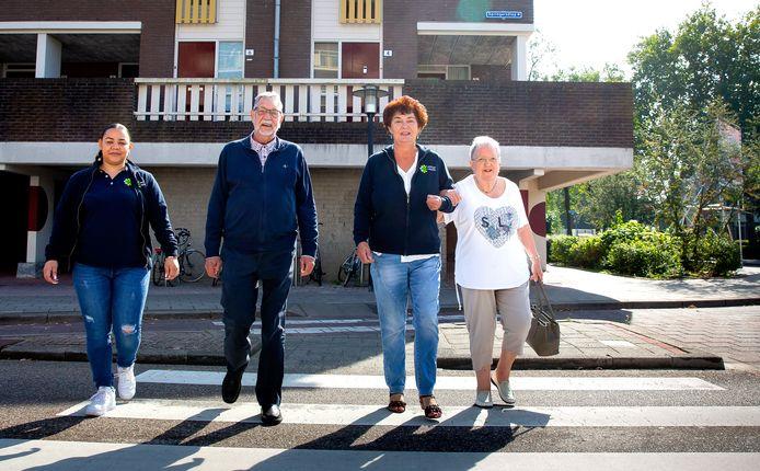 De ouderencoaches Lientje Cristian (links) en Esther Schouten (tweede van rechts) wandelen met Herman van Leeuwen (80) en de een jaar oudere Janny van den Boom door Capelle aan den IJssel.
