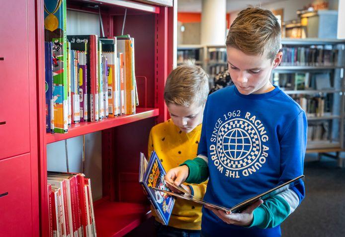 Teun (blauwe shirt) en broer Mees neuzen in boeken die ze dit keer misschien mee naar huis nemen.