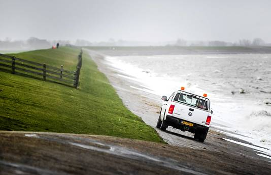 Een auto van Wetterskip Fryslan op een dijk bij Lauwersoog.