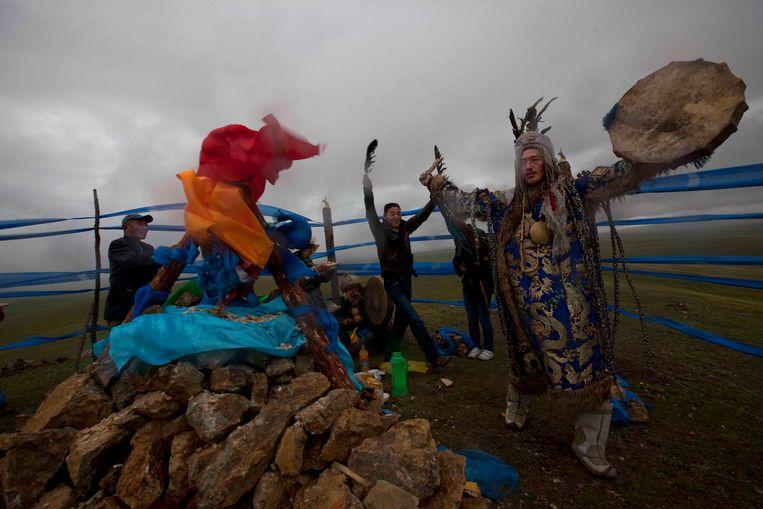 Een sjamanistisch ritueel op een heilig stukje grond in Mongolië. Rechts drinkt een sjamaan melk nadat hij uit een trance komt, daarboven neemt een sjamaan deel aan een vergevingsritueel. Beeld EPA