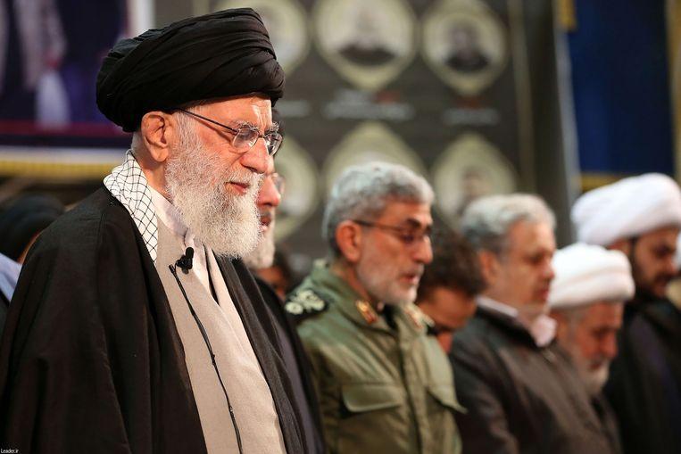 De hoogste leider van Iran, ayatollah Ali Khamenei, leidt het gebed bij de kist van de geliquideerde generaal Qassem Soleimani. Diens opvolger Qaani (in legeruniform) staat vlak bij hem.  Beeld AFP