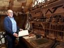Ad van Heesbeen met een oud kasboek van een timmerman.