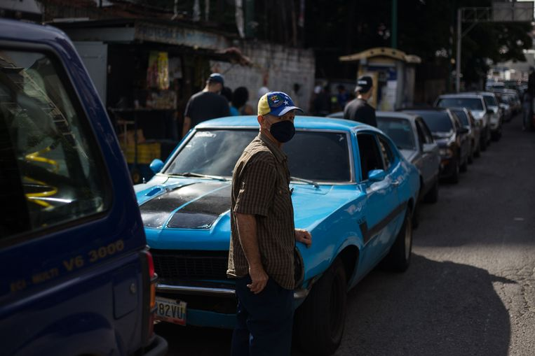 Een inwoner van Caracas staat bij zijn auto in een gigantische rij wachtenden voor benzine. Beeld Hollandse Hoogte / AFP