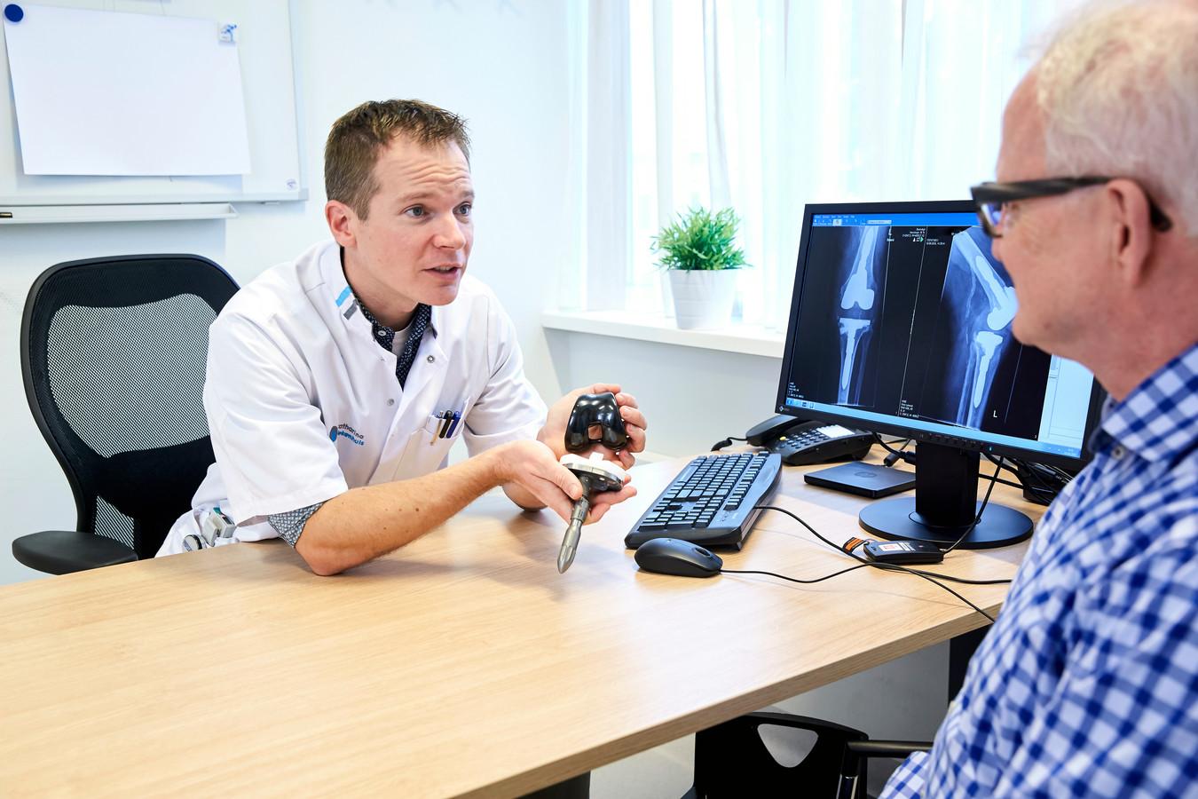 Orthopeed Robin van Kempen van het Catharina Ziekenhuis in gesprek met een patiënt (archieffoto van voor corona-tijd).
